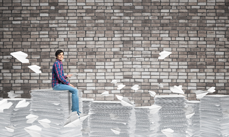 Young man in casual clothing sitting among flying paper planes with brick wall on background. Mixed media.