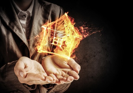 Closeup of businessman in black suit keeping flaming house symbol in hands with dark wall on background. Stock Photo