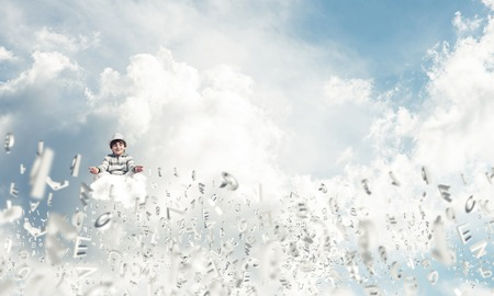 Young little boy keeping eyes closed and looking concentrated while meditating among flying letters in the air with cloudy skyscape on background.