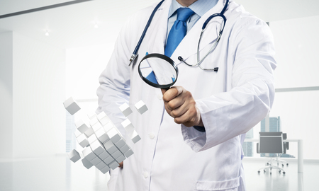 Horizontal shot of young professional doctor in white medical uniform studying multiple cubes in his hands while standing inside bright office building.