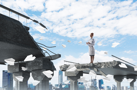 Young female doctor using smart phone while standing among flying paper planes at the edge of broken bridge with cityscape view on background. Medical industry concept