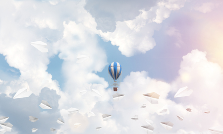 Colorful aerostat flying among paper planes and over the blue cloudy sky. 3D rendering.