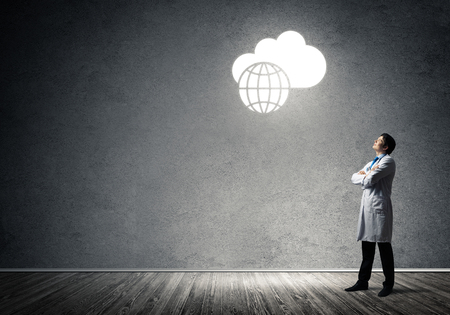 Professional medical industry employee interracting with conceptual glowing cloud while standing inside empty room and gray wall on background.