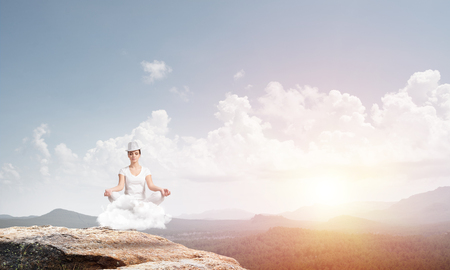 Young woman keeping eyes closed and looking concentrated while meditating on cloud in the air with beautiful and breathtaking landscape on background.
