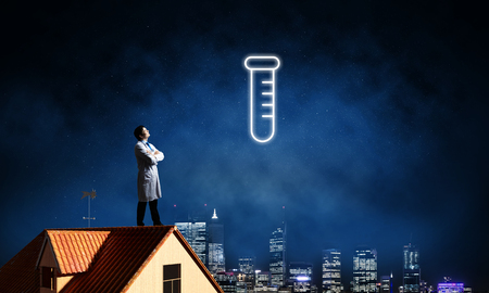 Horizontal shot of young confident doctor in white medical uniform interracting with glowing vial symbol whie standing on brick roof with night sky on background.