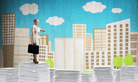 Business woman in suit standing on pile of documents and looking at watch with sketched cityscape view on background. Mixed media. Stock Photo