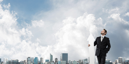 Horizontal shot of young businessman in suit keeping big white arrow in hands while standing against modern cityscape view. Modern business concept Banco de Imagens - 115372126