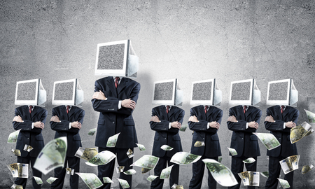 Businessmen in suits with monitors instead of their heads keeping arms crossed while standing in a row among flying euro banknotes in empty room with gray wall on background. Фото со стока