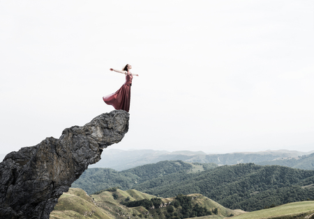 Young attractive woman relaxing in summer day standing on rock top 스톡 콘텐츠