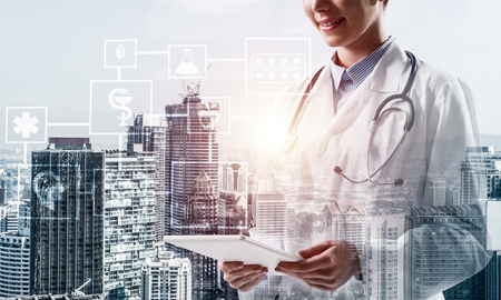 Cropped image of confident medical industry employee standing outdoors and holding tablet in hands. Young female doctor using tablet. Double exposure with medical interface icons