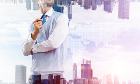 Double exposure of confident and young businessman in smart-casual wear smoking pipe and two modern urban worlds with media map of the world. Concept of global business. Imagens - 115499528
