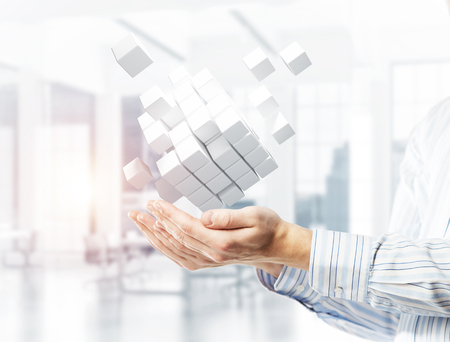 Close of businessman hand holding cube figure as symbol of innovation. 3D rendering Stockfoto