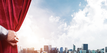 Human hand opens red velvet curtain to modern cityscape and cloudy sky Stock Photo - 115833053