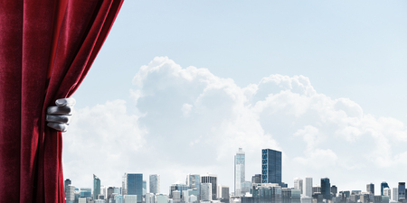 Human hand in glove opens red velvet curtain to modern cityscape Stock Photo