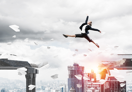 Business woman jumping over gap with flying paper planes in concrete bridge as symbol of overcoming challenges. Cityscape with sunlight on background. 3D rendering. Imagens