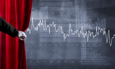 Close up of hand in white glove open red velvet curtain to infographs