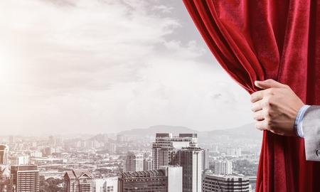 Hand of businessman opening red velvet curtain and cityscape at background Foto de archivo - 115989941