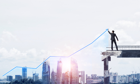 Businessman in suit drawing graphs on modern statistical media interface while standing on broken bridge with cityscape and sunlight on background. 3D rendering.