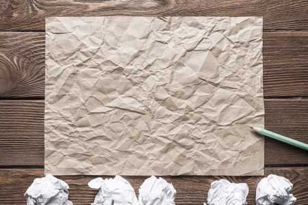 Crumpled brown paper sheet and pencil on wooden table Stock Photo - 115989894