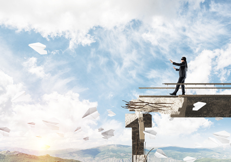 Businessman walking blindfolded on concrete bridge with huge gap as symbol of hidden threats and risks. Skyscape and nature view on background. 3D rendering. Banco de Imagens