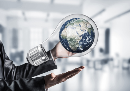 Closeup of business woman in suit holding in hands lightbulb with Earth globe inside with office view background. Elements of this image are furnished by NASA