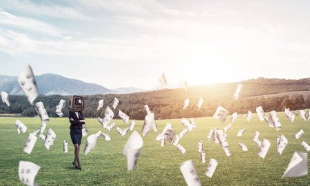 Business woman in suit with an old TV instead of head keeping arms crossed while standing on the road among flying papers with beautiful landscape on background.