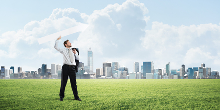 Young and confident businessman in suit starting launching huge white arrow to the air while standing on green lawn and cityscape view on background