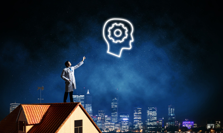 Conceptual image of confident doctor in white uniform interracting with glowing gear brain symbol while standing on brick roof against night cityscape view on background.