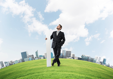 Conceptual image of young businessman in suit looking upside and holding big white arrow in hand while standing on green meadow and cityscape view on background.