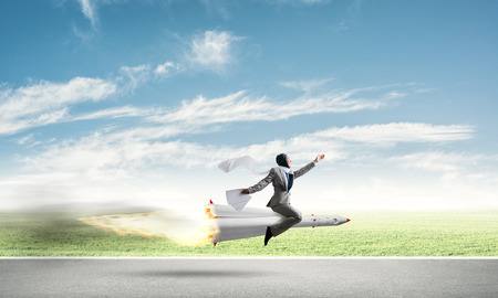 Conceptual image of young businessman in suit flying on rocket above asphalt road with blue cloudy sky on background. 免版税图像