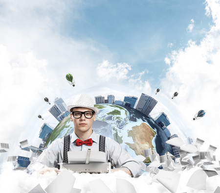 Young man writer in hat and eyeglasses using typing machine while sitting at the table with flying papers and Earth globe among cloudy skyscape on background. Stock Photo