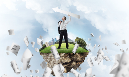 Conceptual image of young and confident business man in suit holding big white arrow in hands while standing on flying island against cloudy skyscape view on background.