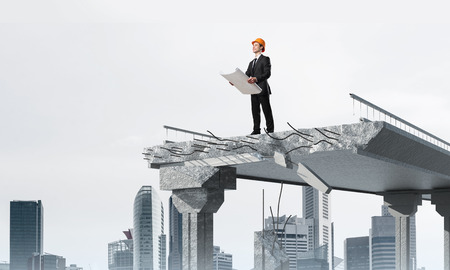 Confident engineer in helmet keeping drawing in hands while standing on broken bridge with cityscape on background. 3D rendering. Stock Photo