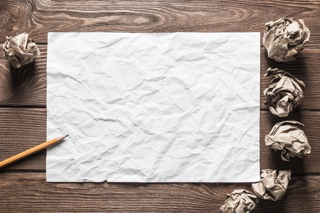 Close up of sheet of white paper and pencil on wooden table Stock Photo