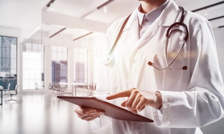 Close up conceptual image of young medical industry employee touching screen of tablet while standing inside white hospital building. Woman doctor with modern gadget in hands Stock Photo
