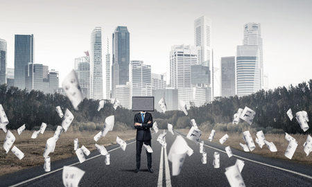 Businessman in suit with TV instead of head keeping arms crossed while standing on the road among flying papers with beautiful landscape on background.