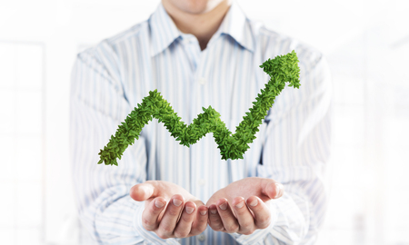 Palms of businessman in suit presenting green plant in form of growing graph. Mixed media