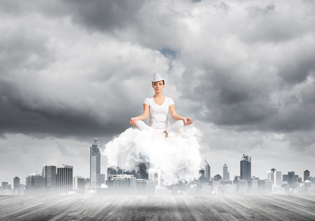 Woman in white clothing keeping eyes closed and looking concentrated while meditating on cloud above wooden floor with cityscape view on background.
