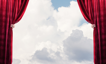 Human hand opens red velvet curtain on blue sky background