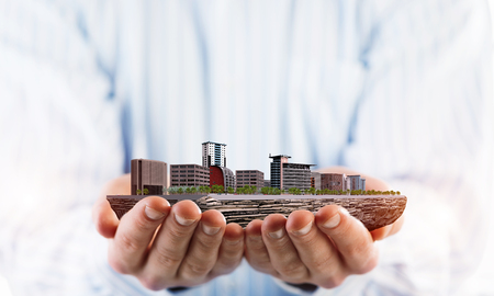 Close up of businessman holding modern office center model in hands. Mixed media Banco de Imagens