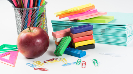 Apple plasticine and school supplies on white table as school concept