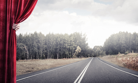 Human hand opens red velvet curtain to landscape with road