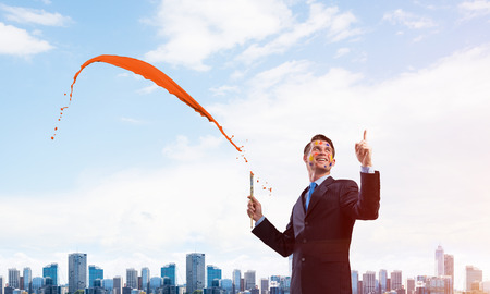 Conceptual image of ambitious and creative businessman in black suit holding paintbrush in hand and looking away while standing with orange splash against cityscape view on background. Imagens