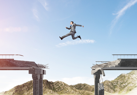 Businessman jumping over huge gap in concrete bridge as symbol of overcoming challenges. Skyscape and nature view on background. 3D rendering. Stockfoto