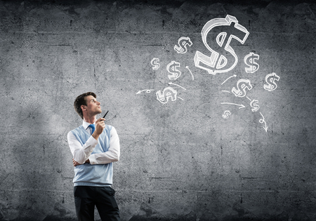 Young businessman smoking pipe with drawn dollar signs at background