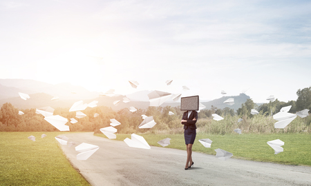 Business woman in suit with TV instead of head keeping arms crossed while standing on the road among flying paper planes with beautiful landscape on background.