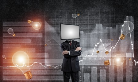 Businessman in suit with TV instead of head keeping arms crossed while standing against flying bulbs and analytical charts drawn on wall on background. Stock Photo