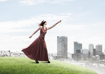 Young attractive woman relaxing in summer day against cityscape background