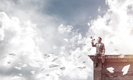 Young businessman sitting on roof and screaming emotionally in megaphone Stok Fotoğraf