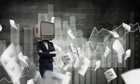 Business woman in suit with old TV instead of head keeping arms crossed while standing against flying papers and analytical charts drawn on dark wall on background.